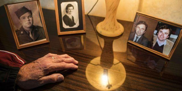La main d'André Gantois repose sur les photos de ses parents, Wilburn Henderson, à gauche, et de sa mère, Irene Gantois, et à droite, un portrait en deux parties représentant André Gantois, à gauche, et son frère, Allen Henderson, de jeunes hommes.
