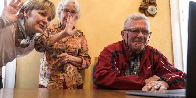 Sur cette photo prise le 8 mai 2019, André Gantois, son épouse Rosine, au centre, et sa fille Isabelle parlent à son demi-frère Allen Henderson, des États-Unis, lors d'une vidéoconférence à Ludres, dans l'est de la France.