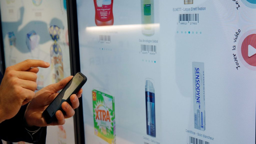 "Head Of Innovation at Groupe Casino, uses his mobile phone at the digital wall to select the items as he shops inside a high-tech store named ""Le 4 Casino"" in Paris, France, October 4, 2018"