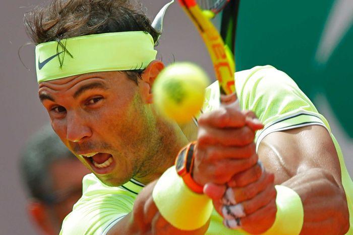 Rafa Nadal ouvre la bouche et utilise ses deux mains pour frapper la balle avec un haut jaune