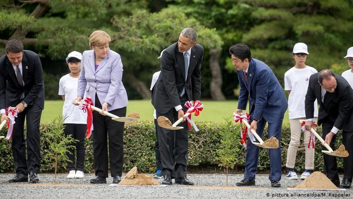 La chancelière allemande Angela Merkel plante un arbre à Ise-Shima, au Japon, à côté de l'ancien président américain Barack Obama