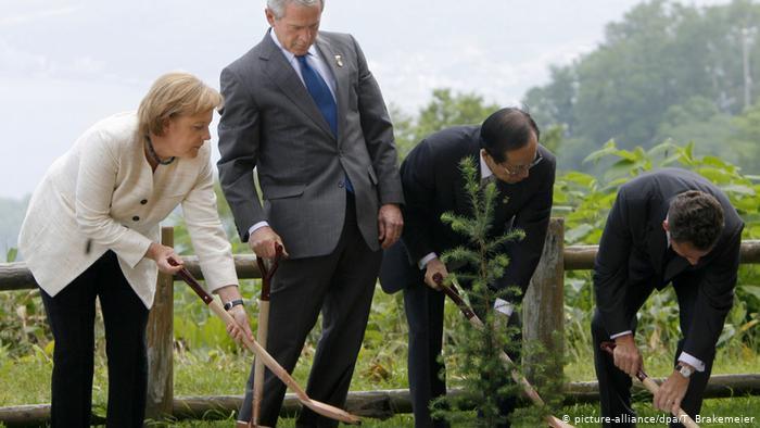 La chancelière allemande Angela Merkel plante un arbre à côté de l'ancien président américain George W. Bush