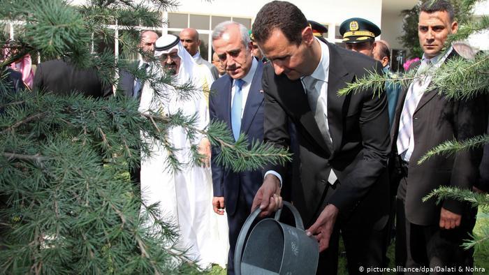 Le président syrien Bashar Assad arrose un arbre près du défunt roi saoudien Abdallah