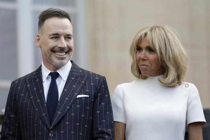 La femme du président français Brigitte Macron (à droite) et David Furnish, le mari de l'auteur-compositeur-interprète britannique Elton John, se tiennent dans la cour de l'Elysée à Paris, le 21 juin 2019,
