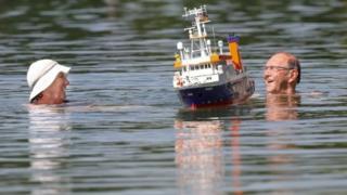 Un couple passe devant un modèle de bateau sur les lacs de Schwarzachtal, dans le sud de l'Allemagne