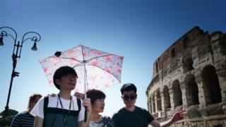 Les touristes s'abritent du soleil avec des parapluies devant le Colisée à Rome le 25 juin 2019 lors d'une vague de chaleur.