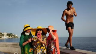Un homme se promène pendant que des touristes prennent des selfies sur la Côte d'Azur, ville de Nice, le 24 juin 2019, alors que les températures montent à 33 degrés Celsius.