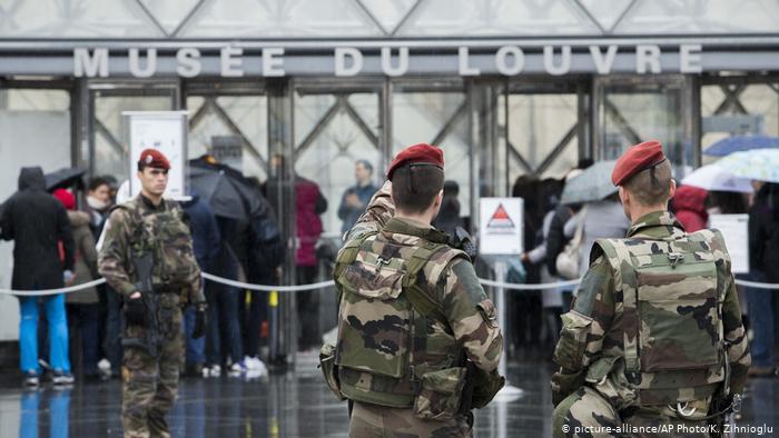 Les soldats montent la garde devant le Louvre et désignent le bâtiment (picture-alliance / AP Photo / K. Zihnioglu)