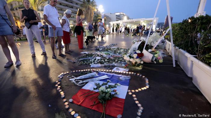 Les gens regardent les hommages des bougies et des fleurs sur la promenade de la promenade à Nice (Reuters / E. Gaillard)
