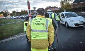 Homme en gilet jaune sur lequel il est écrit 'stop the taxes' en français