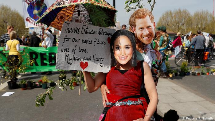 Des militants du changement climatique affichent une pancarte en portant des masques représentant le prince britannique Harry et Meghan, la duchesse de Sussex, lors de la manifestation contre la rébellion Extinction au pont de Waterloo à Londres (Reuters / P. Nicholls)