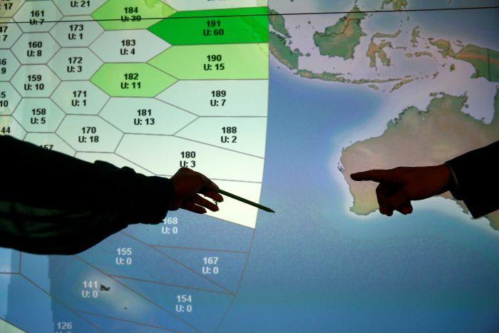 Un membre du personnel de la société de communications par satellite Inmarsat pointe vers une zone de recherche MH370.