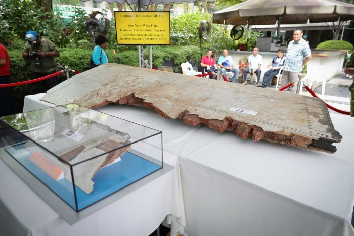 Un gros morceau de débris du vol Malaysia Airlines manquant est affiché à côté d'un morceau plus petit dans une vitrine.
