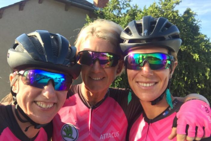 Gros plan des trois membres de l'équipe dans leurs tenues de cyclisme roses.