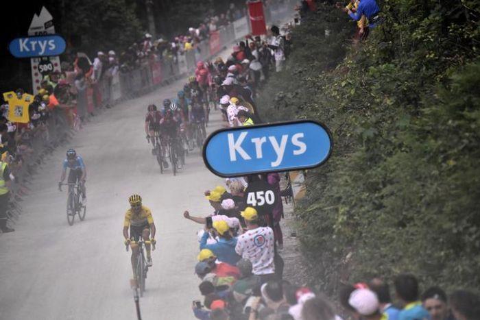 Mikel Landa d'Espagne est vu en train de rouler devant un chemin de terre avec un groupe de cyclistes derrière lui. Les gens bordent la route.