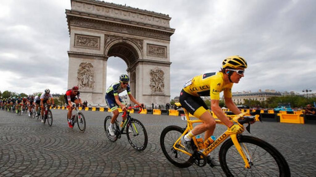 FILE - In this July 29, 2018 file photo, Tour de France winner Britain's Geraint Thomas, wearing the overall leader's yellow jersey, passes the Arc de Triomphe during the twenty-first stage of the Tour de France cycling race over 116 kilometers (72.1 miles) with start in Houilles and finish on Champs-Elysees avenue in Paris, France. Chris Froome's absence, coupled with the withdrawal of last year's runner-up Tom Dumoulin, has reshuffled the game and produced a long list of top contenders.