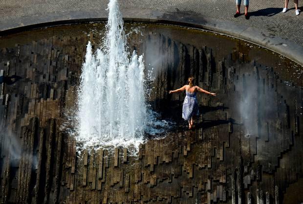 Une femme se refroidit dans une fontaine le 26 juin 2019 au Lustgarten, dans le centre de Berli. Photo de Tobias SCHWARZ / AFP