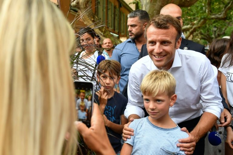 French President Emmanuel Macron (C) on Saturday posed for pictures in Bormes-les-Mimosas, near the fort of Bregancon where he will host his Russian counterpart Vladimir Putin in August (AFP Photo/GERARD JULIEN)